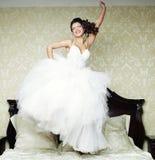 愉快的新娘在床上跳。 库存图片