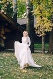 愉快的新娘在自然的振翼的礼服摆在 附庸风雅 库存图片
