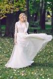 愉快的新娘在自然的振翼的礼服摆在 附庸风雅 库存照片