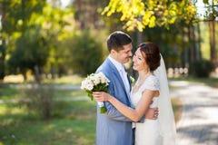 愉快的新娘,站立在绿色公园的新郎,亲吻,微笑,笑 恋人在婚礼之日 耦合愉快的爱年轻人 免版税库存照片