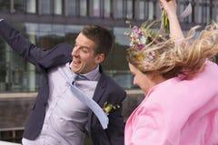 愉快的新婚佳偶与跳和微笑喜悦的婚姻的夫妇夫妇结婚 免版税库存图片