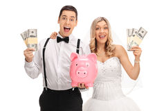 愉快的新婚佳偶加上piggybank和金钱捆绑 库存照片