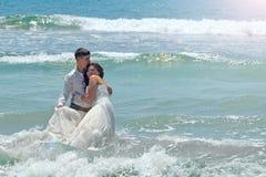 愉快的新婚佳偶在印度洋的水域中拥抱并且笑 晴朗的婚礼之日和蜜月在海岛上的热带 库存图片