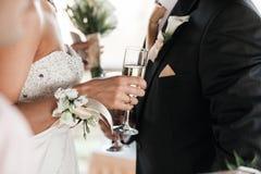 愉快的新婚佳偶夫妇喝白色婚礼香槟酒 装饰的水晶玻璃 新娘和新郎的手与金子 图库摄影
