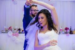 愉快的新婚佳偶夫妇获得乐趣在他们的第一个舞蹈期间在婚姻 免版税库存照片