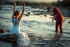 愉快的新婚佳偶情感室外画象  新郎在他迷人的新娘飞溅水 免版税库存图片
