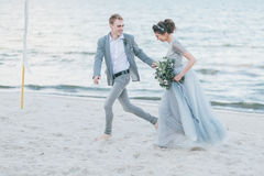 愉快的新婚佳偶有乐趣和赛跑由海 免版税库存照片