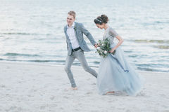 愉快的新婚佳偶有乐趣和赛跑由海 库存图片