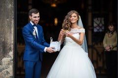 愉快的新婚佳偶从教会出来和投掷糖果的丈夫和妻子 免版税库存图片