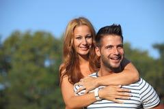 愉快的新恋人获得乐趣在公园 免版税图库摄影