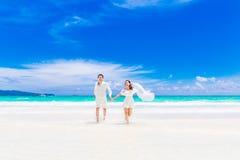 愉快的新郎和新娘含沙热带海滩的 婚礼和h 免版税图库摄影
