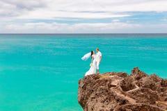 愉快的新郎和新娘岩石的 backgrou的绿松石海 库存图片