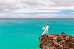 愉快的新郎和新娘岩石的 backgrou的绿松石海 免版税图库摄影