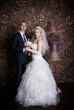 愉快的新郎和迷人的新娘有花束的从玫瑰在演播室 免版税库存图片