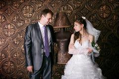 愉快的新郎和迷人的新娘有花束的从玫瑰在演播室 库存照片