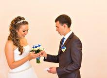 愉快的新郎戴着婚戒他的新娘 庄严的结婚登记 免版税库存照片