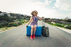 愉快的旅客妇女坐在路和笑的一个手提箱 旅行,旅途,旅行的概念 免版税库存照片