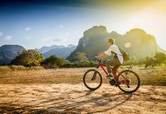 愉快的旅游妇女在山区的骑一辆自行车在老挝 T 免版税库存图片