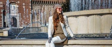 愉快的旅游妇女在米兰,坐在喷泉附近的意大利 库存照片