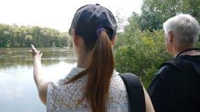 愉快的旅行概念 一起人和女孩远足 有背包的徒步旅行者 他们在河岸停止并且看它 股票视频