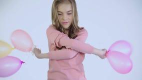 愉快的无忧无虑的女孩使用与气球在背景的照相机 股票录像