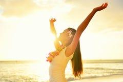 愉快的无忧无虑的妇女在夏威夷海滩日落释放 免版税库存照片