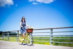 愉快的无忧无虑的妇女在礼服骑马葡萄酒自行车和蓝色sk 免版税库存图片