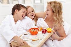 愉快的早晨-用早餐在妈妈的床上 免版税库存照片