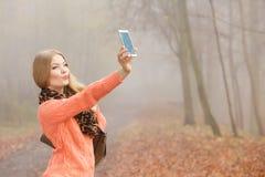 愉快的时尚妇女在拍selfie照片的公园 免版税图库摄影