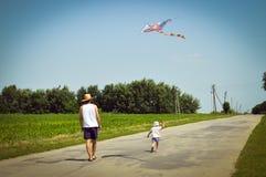 愉快的时期:获得的父亲&的儿子的图象使用与风筝的乐趣户外在夏天晴天绿色森林&蓝天 免版税库存图片