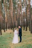 愉快的时髦的新婚佳偶对在浪漫年轻夏天杉木森林里 免版税库存图片