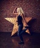愉快的时髦青少年的女孩跳舞和跳跃在黄色星和增殖比 免版税库存图片