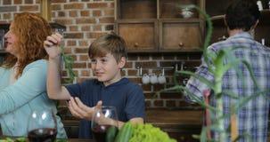 愉快的晚餐、的父母和谈话两个的孩子的家庭繁忙的烹调鲜美膳食在厨房里,当准备食物时 股票录像