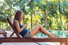 愉快的智能手机妇女松弛近的游泳池 使用她的手机app 4g数据的美丽的女孩演奏歌曲,当放松时 免版税库存照片