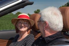 愉快的更旧的夫妇驾驶与在自然的豪华跑车在一个晴天 免版税图库摄影