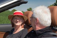 愉快的更旧的夫妇驾驶与豪华敞篷车汽车 免版税库存图片