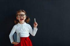 愉快的有书的女小学生学龄前女孩在学校黑板附近 免版税库存照片