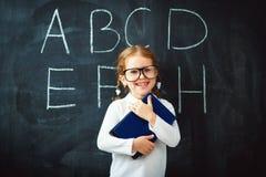愉快的有书的女小学生学龄前女孩在学校黑板附近 免版税图库摄影