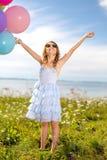 愉快的有五颜六色的气球的女孩挥动的手 库存图片