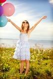 愉快的有五颜六色的气球的女孩挥动的手 免版税图库摄影