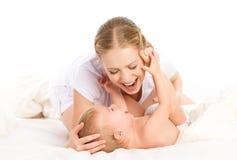 愉快的有家庭母亲和的婴孩乐趣使用,笑在床上 免版税图库摄影