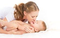 愉快的有家庭母亲和的婴孩乐趣使用,笑在床上 免版税库存照片