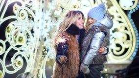 愉快的有母亲和小俏丽的女儿一起享受与烟花闪烁发光物的美好时光圣诞节假日 股票录像