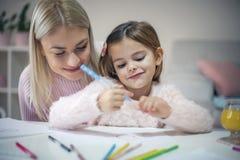 愉快的有母亲和的女儿教育 免版税库存照片