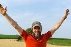 愉快的有胡子的人举了他的手对在一个金黄夏天玉米的天空归档,与开放胳膊 免版税库存照片