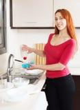 愉快的有洗涤剂的主妇洗涤的板材 免版税库存照片