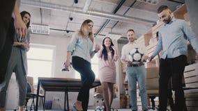 愉快的朋友使用与球在现代健康办公室 临时雇员在断裂慢动作时享受体育活动 股票视频
