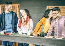 愉快的朋友吃午餐在吃烤肉和喝红酒-有的恋人两对夫妇的后院滑稽的天 库存照片