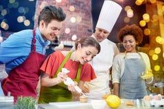 愉快的朋友和厨师在厨房里烹调烘烤 库存图片