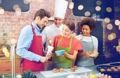 愉快的朋友和厨师在厨房里烹调烘烤 免版税库存照片